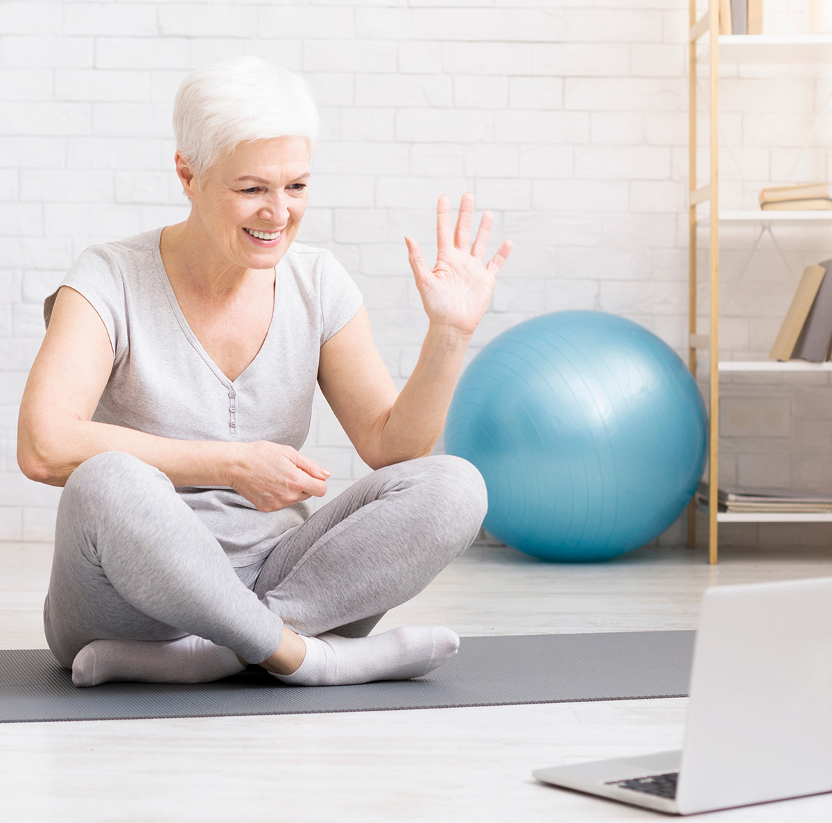 Senior woman stetches and sits cross legged on a yoga mat in front of a laptop