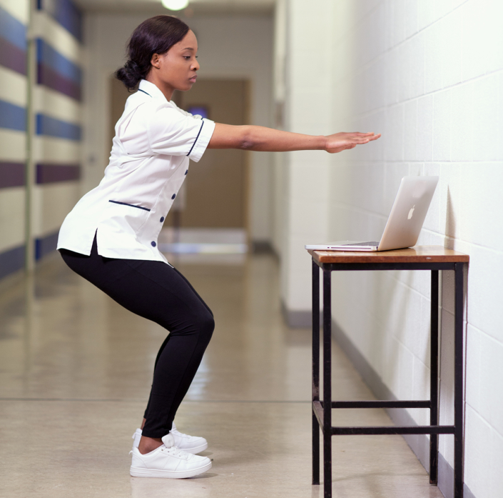 Female nurse squats with arms outreached in front of a laptop at work